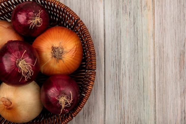 Vista superior de cebollas rojas y amarillas saludables en un balde sobre un fondo de madera gris con espacio de copia