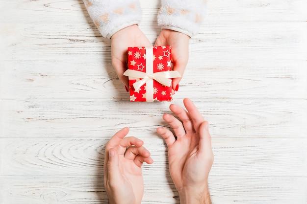 Vista superior de la celebración de un regalo en manos femeninas y masculinas