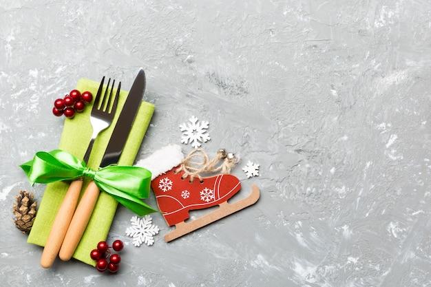 Vista superior de la cena de año nuevo en el fondo de cemento. cubiertos festivos en servilleta con adornos navideños y juguetes. concepto de vacaciones familiares con espacio de copia