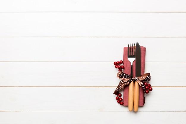 Vista superior de la cena de año nuevo sobre fondo de madera. cubiertos festivos en servilleta con adornos navideños y juguetes. concepto de vacaciones familiares con espacio de copia