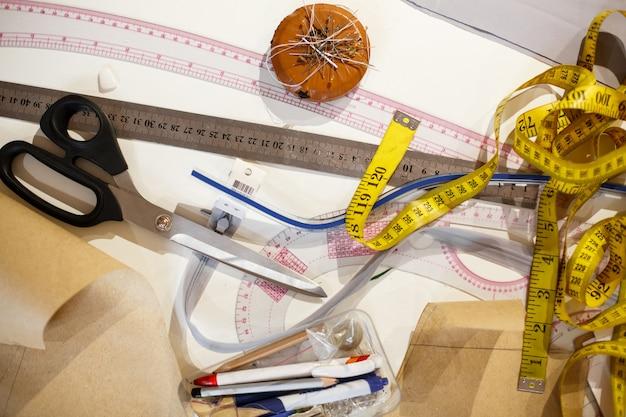 Vista superior de un centímetro amarillo, tijeras, regla y otras herramientas de la costurera. confeccionando ropa