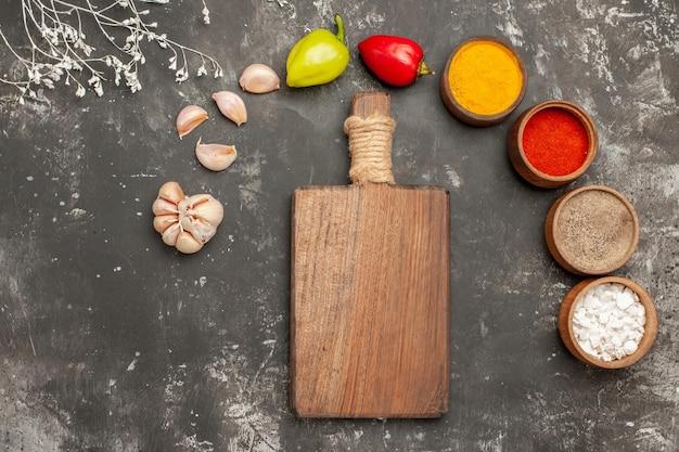 Vista superior de cerca coloridas especias cuatro tipos de especias pimientos de bola de ajo junto a la placa de cocina de madera sobre la mesa