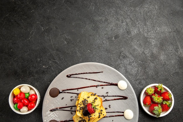 Vista superior de cerca dulces gris placa de trozos de pastel con salsa de chocolate y fresas junto a los tazones de dulces y fresas
