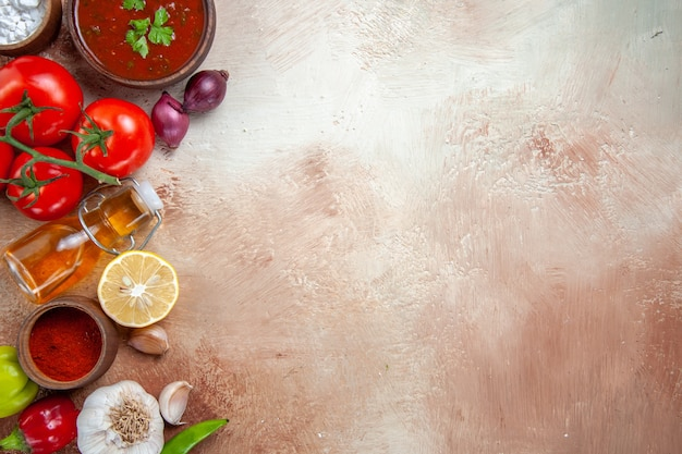 Vista superior de cerca especias especias coloridas cebollas ajo botella de aceite tomates salsa de limón