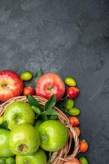 Vista superior de cerca frutas cesta de madera de manzanas verdes y manzanas rojas cerezas frutas cítricas