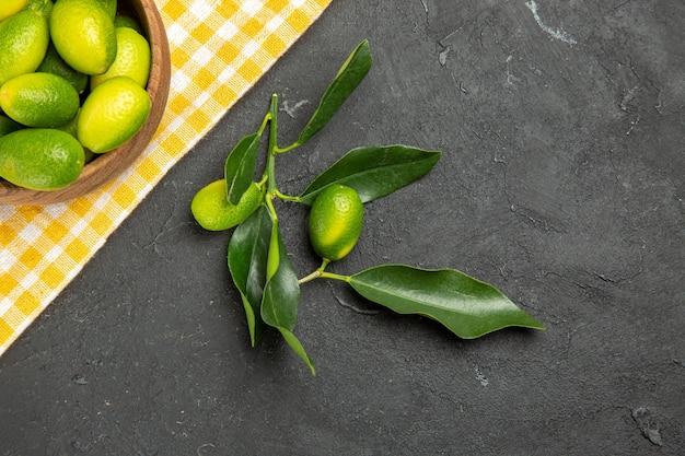 Vista superior de cerca frutas frutas en el recipiente sobre el mantel blanco-amarillo frutas verdes con hojas
