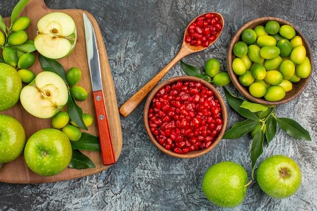 Vista superior de cerca frutas granada cuchara manzanas cítricos manzanas cuchillo en el tablero