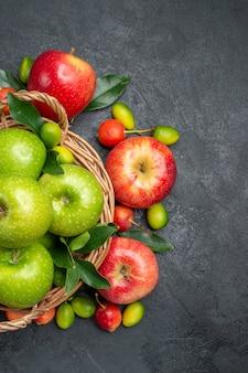 Vista superior de cerca frutas manzanas rojas cerezas frutas cítricas alrededor de la canasta de manzanas verdes