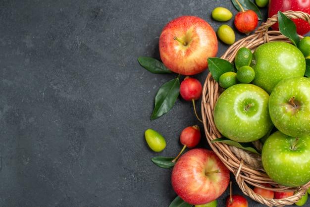 Vista superior de cerca frutas manzanas rojas cerezas frutas cítricas alrededor de la canasta