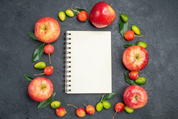 Vista superior de cerca frutas manzanas rojas cerezas frutas cítricas alrededor de cuaderno blanco