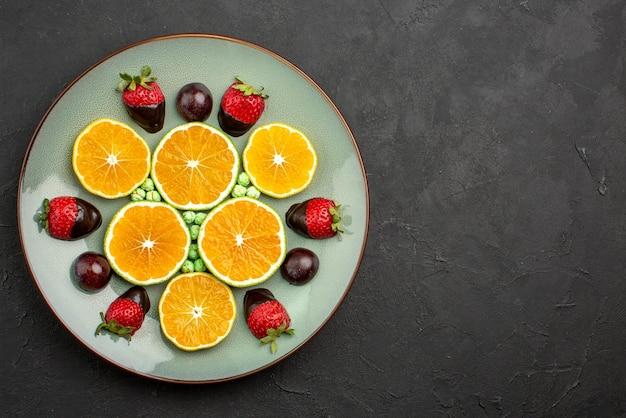 Vista superior de cerca frutas y naranja picada de chocolate con fresas cubiertas de chocolate y caramelos verdes en el lado izquierdo de la mesa oscura