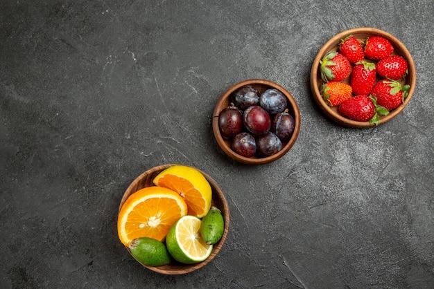 Vista superior de cerca frutas en tazones de mesa de apetitosas bayas y frutas cítricas en la superficie oscura