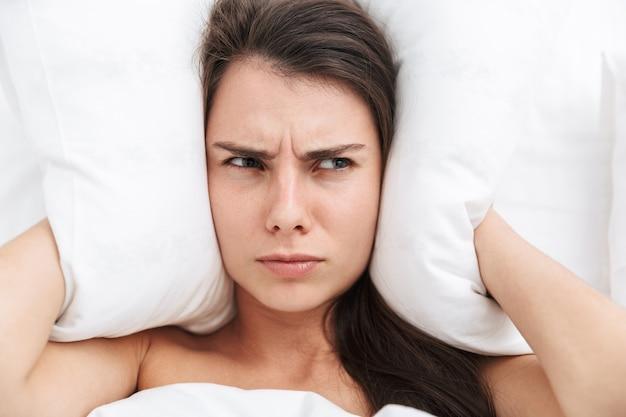Vista superior de cerca de una hermosa joven tendida en la cama, cubrir las orejas con una almohada