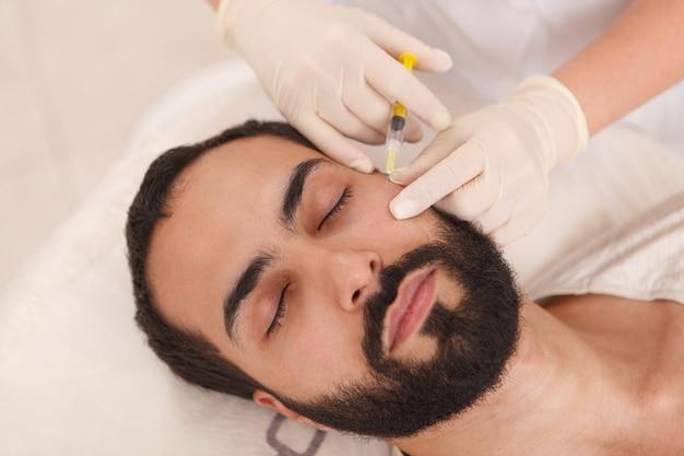 Vista superior de cerca de un hombre barbudo recibiendo inyecciones de relleno anti-envejecimiento en la clínica de belleza