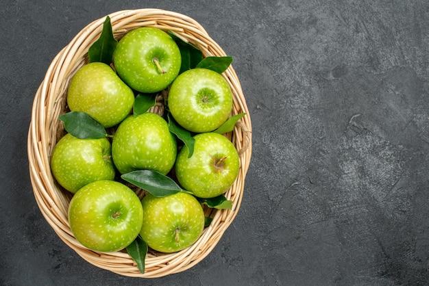 Vista superior de cerca manzanas en la canasta ocho apetitosas manzanas con hojas verdes en la canasta