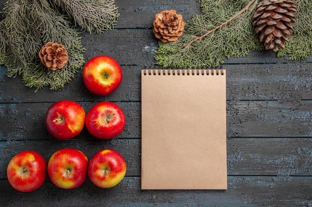 Vista superior de cerca las manzanas y el cuaderno y seis manzanas de color amarillo rojizo sobre una superficie gris junto a las ramas y conos de abeto