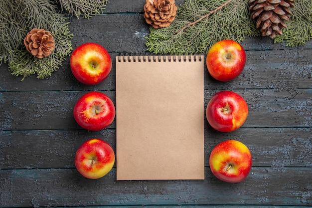 Vista superior de cerca las manzanas y el cuaderno entre seis manzanas de color amarillo-rojo sobre una superficie gris junto a las ramas y conos de abeto