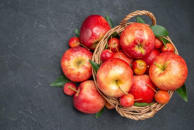 Vista superior de cerca manzanas manzanas de cuerda las apetitosas cerezas en la canasta