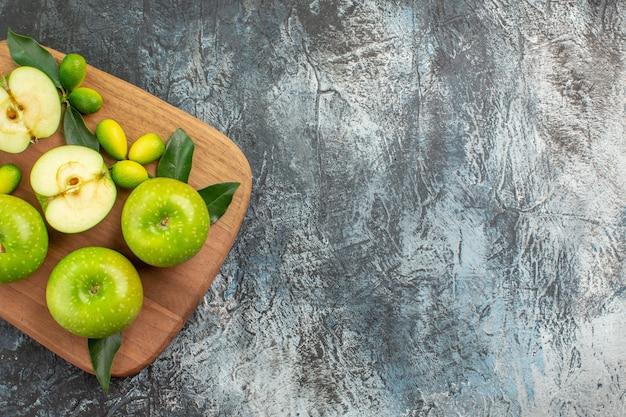 Vista superior de cerca manzanas manzanas verdes cítricos con hojas en el tablero