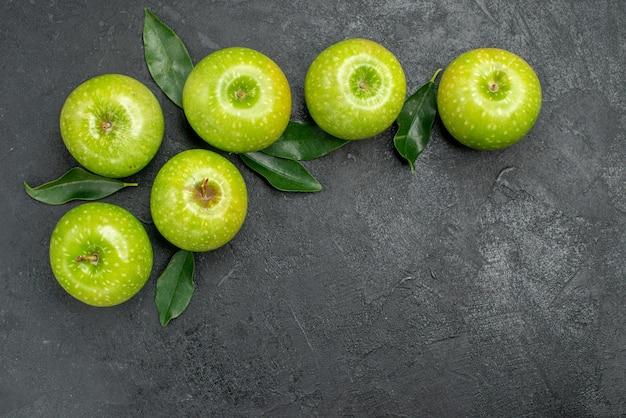 Vista superior de cerca manzanas verdes seis manzanas verdes con hojas sobre la mesa oscura