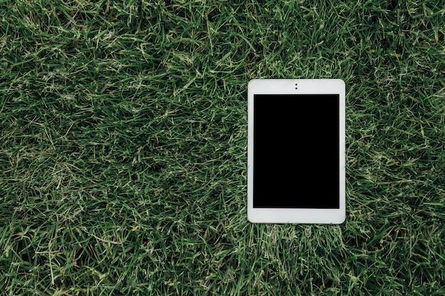 Vista superior de cerca de la tableta blanca acostada sobre la hierba verde en el parque de la ciudad concepto de tecnología digital pantalla táctil negra de libro electrónico portátil con espacio de copia dispositivo de red g mock up