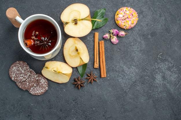 Vista superior de cerca una taza de té rebanadas de manzana palitos de canela galletas una taza de té de hierbas