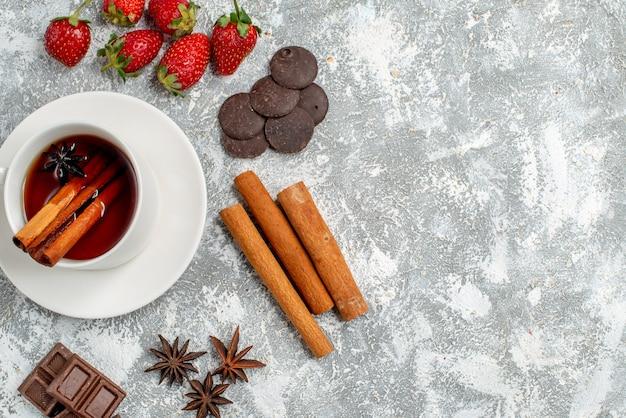 Vista superior de cerca, té de semillas de anís y canela y algunas fresas, chocolates, semillas de anís y canela en el lado izquierdo de la mesa con espacio libre