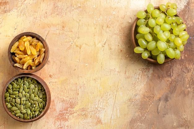Vista superior de cerca las uvas las apetitosas uvas verdes pasas semillas de calabaza en los cuencos marrones
