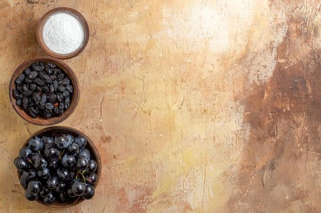 Vista superior de cerca las uvas uvas negras pasas de azúcar en los cuencos marrones