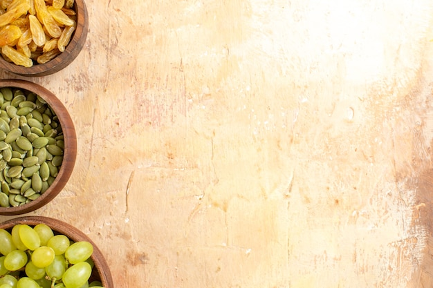Vista superior de cerca las uvas uvas verdes pasas semillas de calabaza en los cuencos marrones