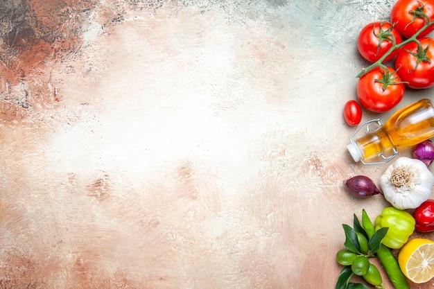Vista superior de cerca verduras tomates con pedicelos ajo pimientos aceite de limón cebolla