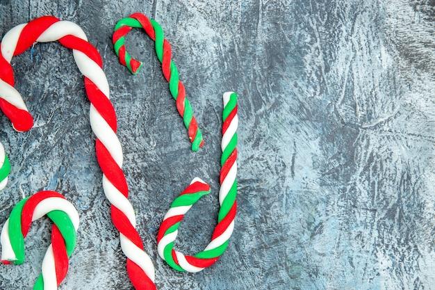 Vista superior cercana caramelos de navidad coloridos sobre fondo gris