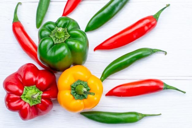 Vista superior cercana de coloridos pimientos con pimientos picantes en el escritorio de luz, producto de ingrediente de comida caliente de especias vegetales