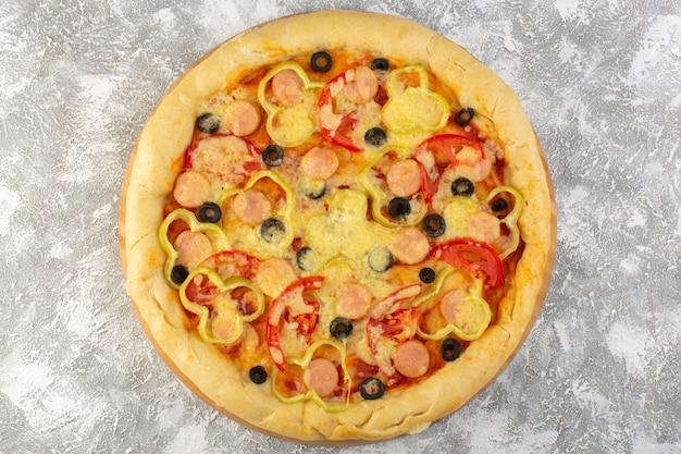 Vista superior cercana deliciosa pizza con queso con aceitunas, salchichas y tomates en el fondo gris comida rápida comida de masa italiana