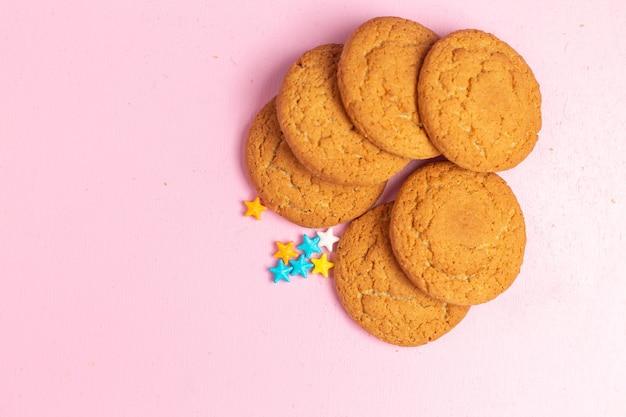 Vista superior cercana deliciosas galletas dulces horneadas forradas en el fondo rosa