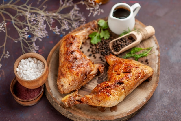 Vista superior cercana delicioso pollo frito con diferentes condimentos en el espacio oscuro