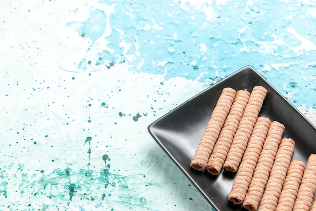 Vista superior cercana dulces galletas largas dentro de molde para pastel negro sobre superficie azul