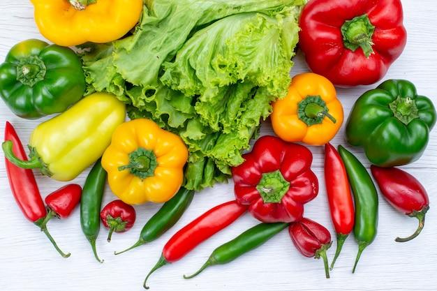 Vista superior cercana de ensalada verde junto con pimientos morrones y pimientos picantes en el escritorio blanco, ingrediente de comida vegetal