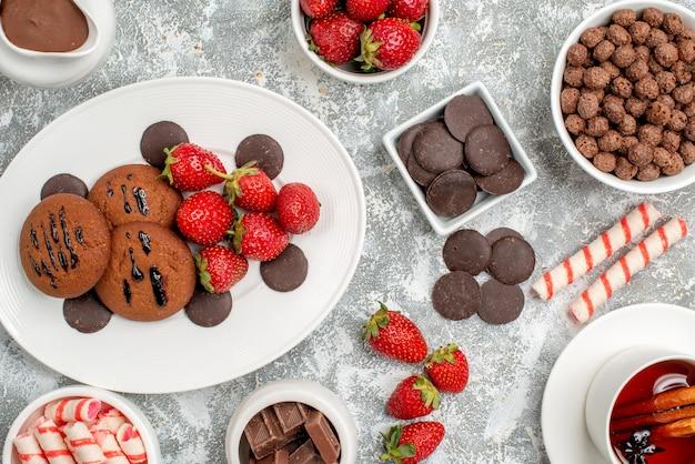 Vista superior cercana galletas fresas y bombones redondos en la placa ovalada cuencos de dulces fresas chocolates cereales cacao y té de canela en la mesa gris-blanca