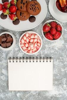 Vista superior cercana galletas fresas y bombones redondos en la placa ovalada cuencos de dulces fresas chocolates té de canela y un cuaderno sobre la mesa gris-blanca