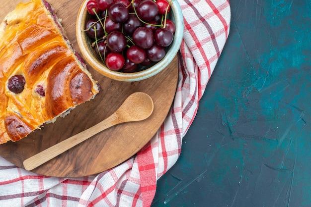 Vista superior cercana de guindas frescas con tarta de cerezas en azul oscuro, tarta de frutas cereza dulce