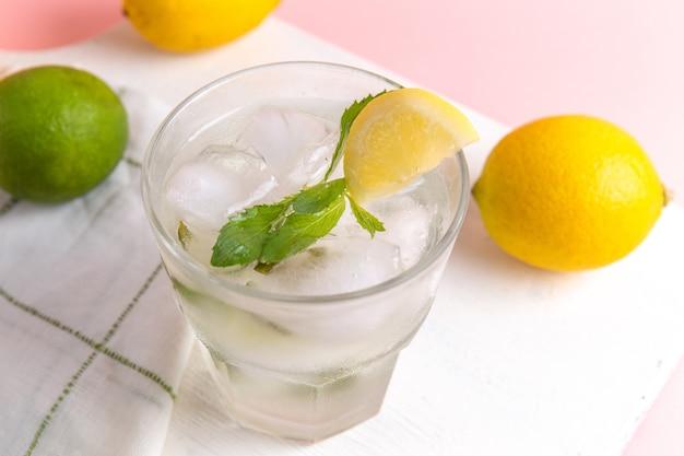 Vista superior cercana de limonada fría fresca con hielo dentro del vaso junto con limones frescos en la superficie rosa