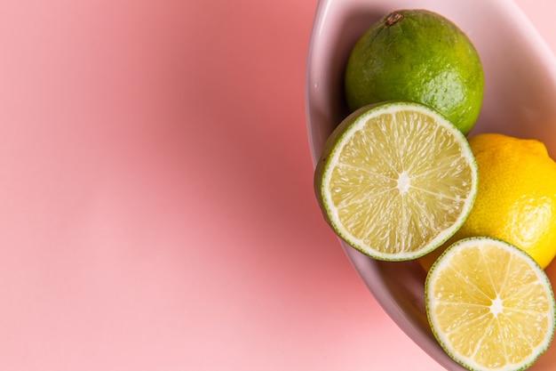 Vista superior cercana de limones frescos con rodajas de limón dentro de la placa en la superficie de color rosa claro