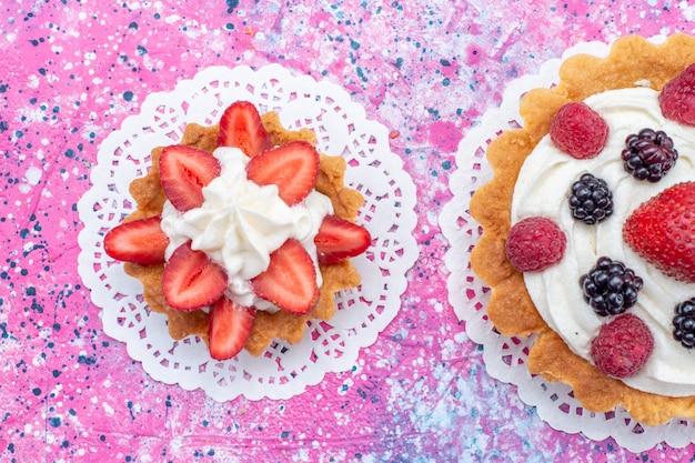 Vista superior cercana de pequeños pasteles cremosos con diferentes bayas en blanco claro