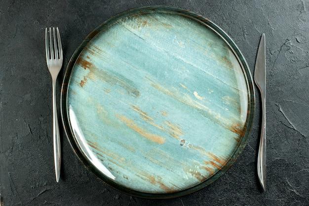 Vista superior cercana plato redondo cuchillo y tenedor sobre mesa negra
