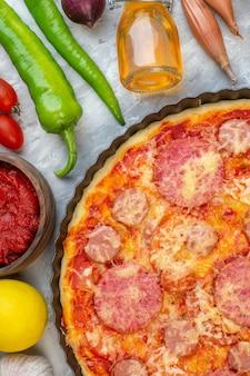 Vista superior cercana sabrosa pizza de salchicha con verduras frescas en blanco