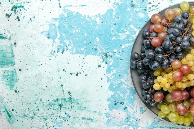 Vista superior cercana uvas frescas de color fruta jugosa y suave sobre superficie azul