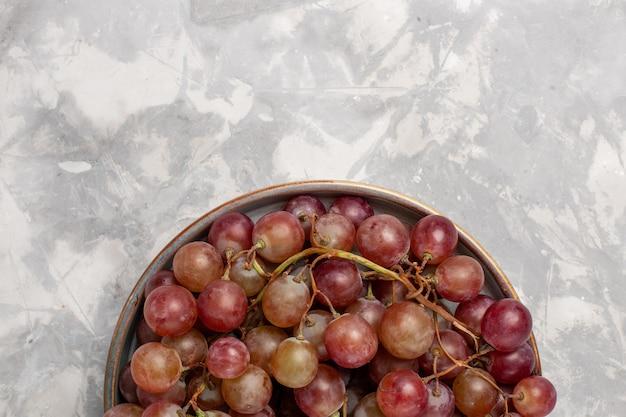 Vista superior cercana uvas rojas frescas jugosas frutas dulces suaves en el escritorio de color blanco claro fruta fresca jugo suave vino