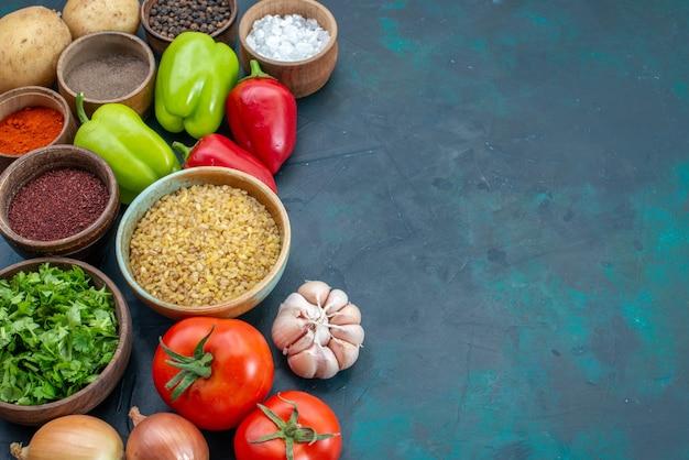 Vista superior cercana de verduras frescas con condimentos y verduras en un escritorio azul oscuro, comida vegetal, comida, platos verdes