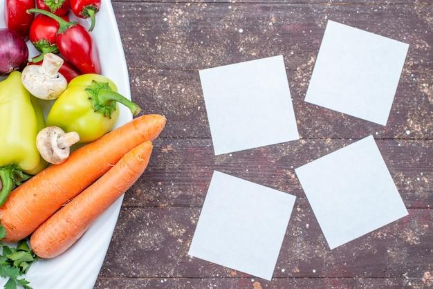Vista superior cercana de verduras frescas con setas dentro de la placa en un plato de setas de comida vegetal marrón